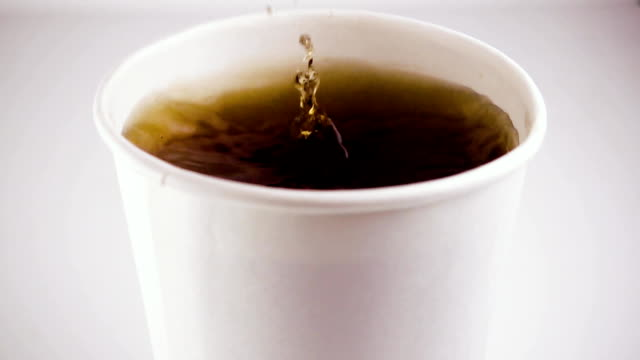 Slow mo. In a glass of tea drops a cube of sugar video