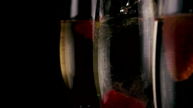 Slow mo. In one of the three glasses with champagne falls strawberries video