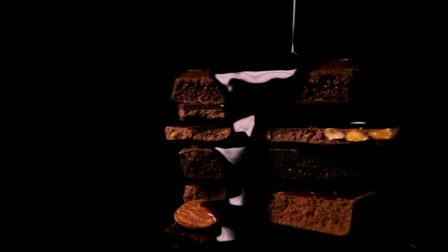 Slow mo. Liquid dark chocolate is poured onto a pile of chocolate video