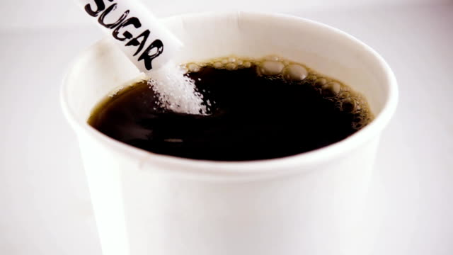 Slow mo. Sugar from a bag with an inscription in coffee video
