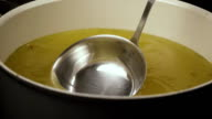 Slow mo. The broth is scooped out with a ladle from the pan video