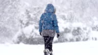 Slow Mo: Young Woman Walking Alone Through Snow Blizzard video