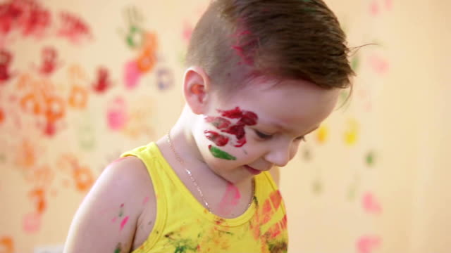 Slow motion and close-up shot of a happy little boy giving tight hugs to his beloved mother while they are playing and leaving their colorful fingerprints on the wall video