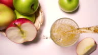 Slow motion apple juice is poured into a glass top view video