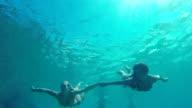 Slow Motion Beautiful Girls in Bikinis Swimming Underwater Holding Hands in Pacific Ocean. video