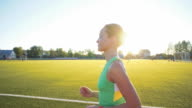 Slow motion. Beautiful young woman exercise jogging and running on athletic track on stadium at sunrise. Cinematic style video video