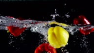 Slow motion bell peppers falling into water with splashes on black background video