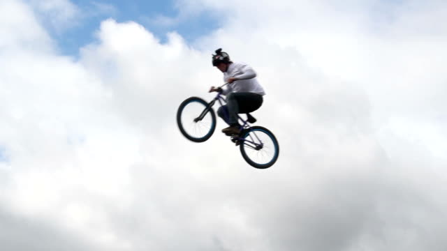 Slow motion bicycle jumper jumps high with bike sky background video