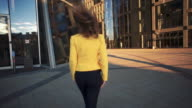 Slow motion. Camera following to Young beautiful girl in a yellow jacket which walking beatween tall buildings. Bright sunlight in the evening. Cinematic style video video