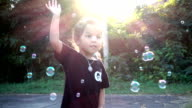 Slow motion capture. Little girls playing soap bubbles video