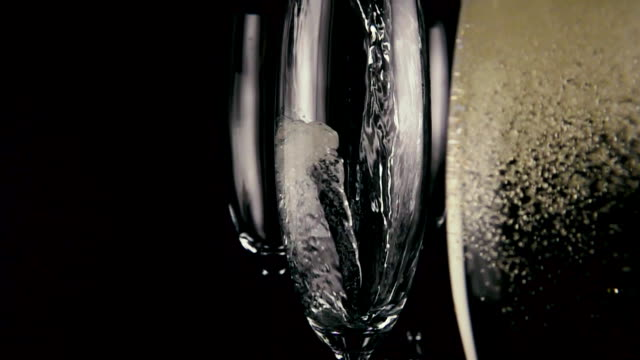 Slow motion. Champagne is poured into one of three glasses video