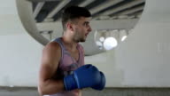 Slow motion. Close up. Boxer is preparing to the fight outdoors on the background of gray concrete walls with circular holes. video