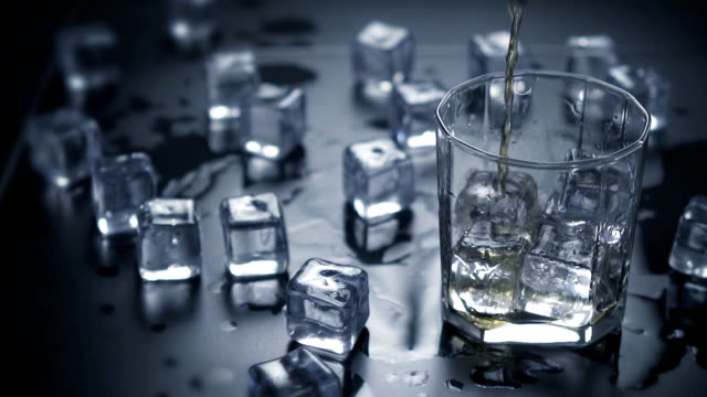 Slow motion. Close up pouring whiskey in glass with ice cubes.dark black background. video