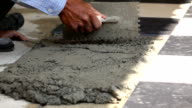 Slow Motion; Construction worker using putty knife tiling floor video