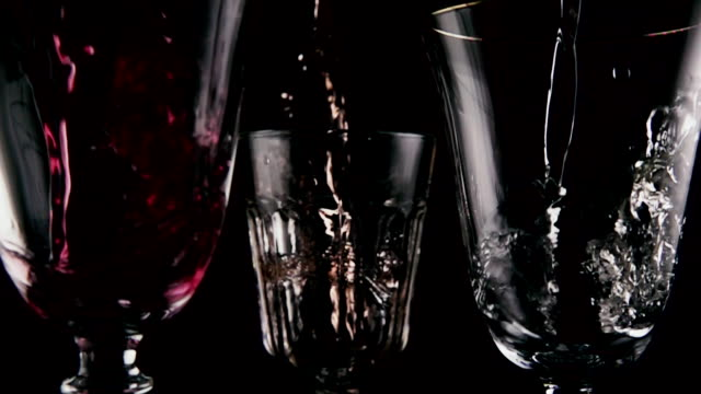 Slow motion. Different wine pour into three glasses video