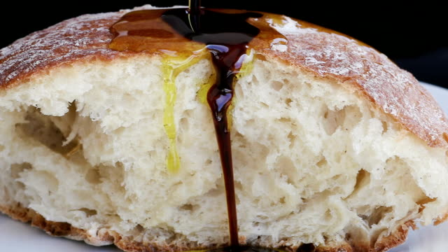 Slow motion extra virgin olive oil and balsamic vinegar being poured over bread video