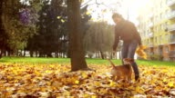 Slow motion footage: female master plays with her pet on an autumnal day just outside their house. video