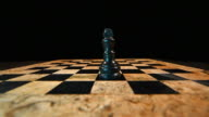 Slow motion footage of a chess board in a dark room with a black king standing on the board, white king hits the black king and takes his place video