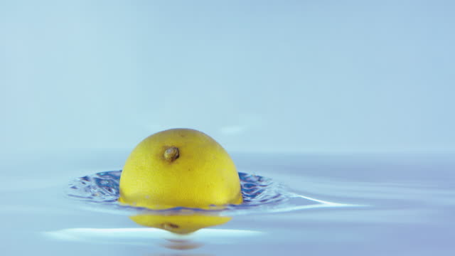 Slow Motion Footage Of A Lemon Falling On A Shiny Water Surface video