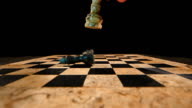 Slow motion footage of a white king chess figure hitting a black king, the black king falls on the board and rolls away video