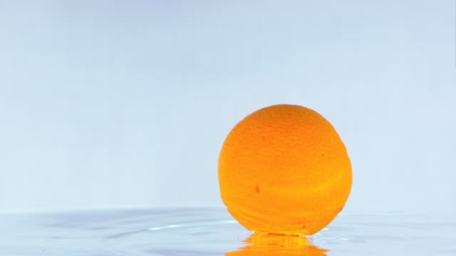 Slow Motion Footage Of An Orange Bumping On Water Surface. video