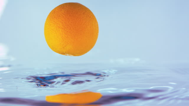 Slow Motion Footage Of An Orange Falling In Shiny Water video