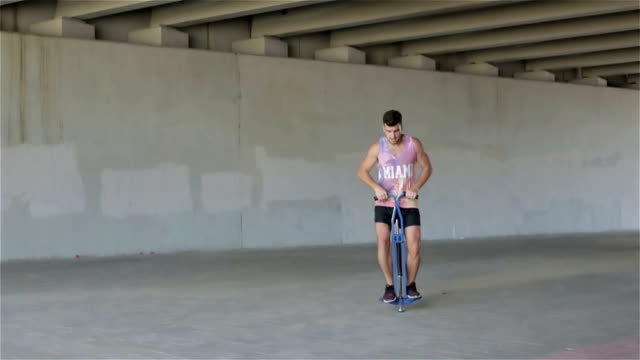 Slow motion. Front view. Young athletic man practicing jumps. video