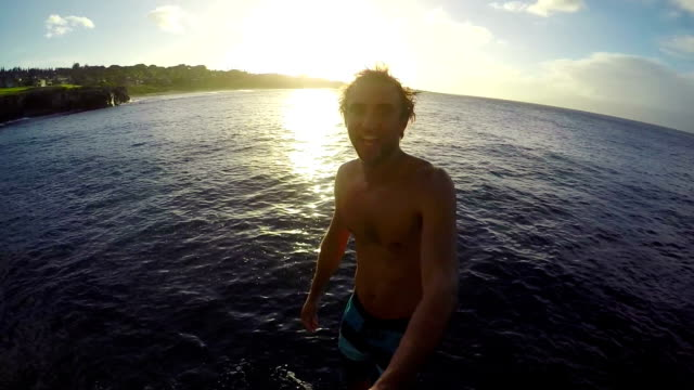 POV Slow Motion GOPRO Selfie Stick Cliff Jumping. Athletic Young Man Jumping From Cliff Into Ocean. video