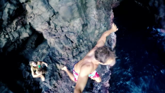 Slow Motion GOPRO POV Young Man Cliff Jump Into Ocean. Selfie Stick video