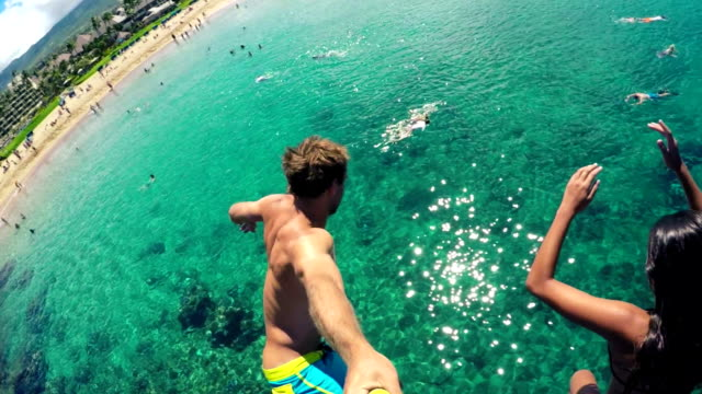 POV GOPRO HD Slow Motion Group of friends jumping from cliff into the ocean in Hawaii. video