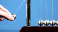 Slow motion: Hand lifts end sphere of Newton's Cradle desk toy and drops it to start the perpetual motion. video