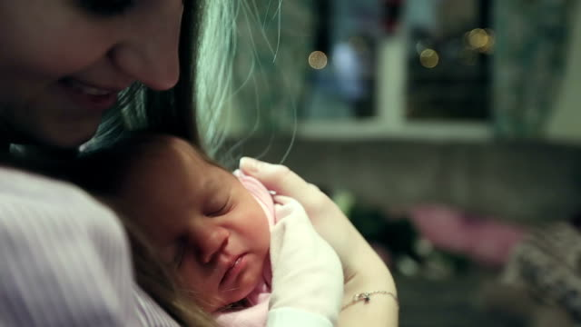 Slow motion. Happy mother holding a newborn baby in her arms in the room. video