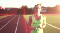 Slow motion. Hot air evoporates. Beautiful young woman exercise jogging and running on athletic track on stadium at sunrise. Cinematic style video video