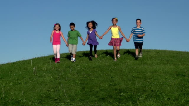 Slow motion kids running down hill holding hands video