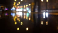 Slow motion lights bokeh circles reflecting in water on night city street with small raindrops video