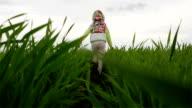 Slow motion. Little girl running on the green field. video