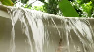 Slow motion low angle of lip of manmade waterfall with Garuda mythic figure video