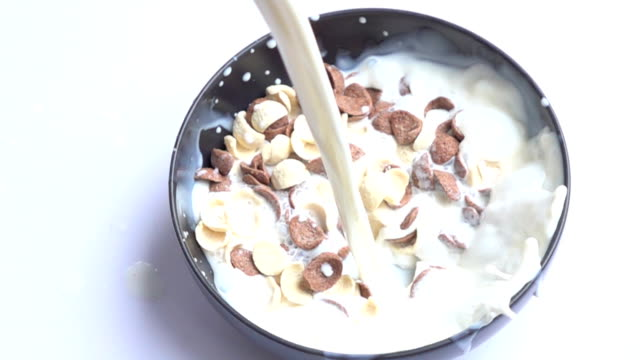 Slow motion milk poured onto cereals video