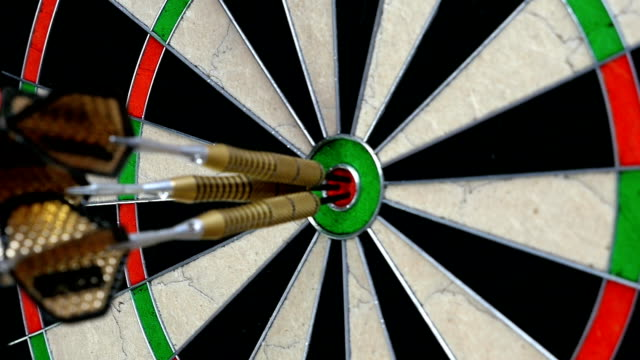 Slow motion of a darts player's hand picking up three darts in bull's eye video