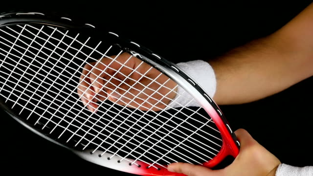 Slow motion of a tennis player's hand adjusting the net of his tennis racket, black background video