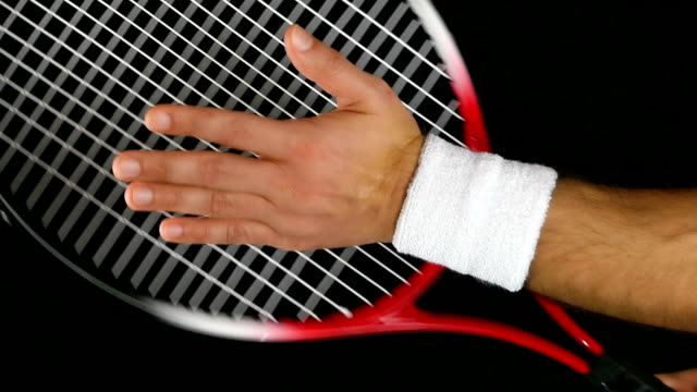Slow motion of a tennis player's hand hitting the net of his tennis racket, black background video