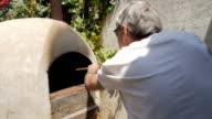 Slow motion of an active senior cleaning a hot wood fired oven video