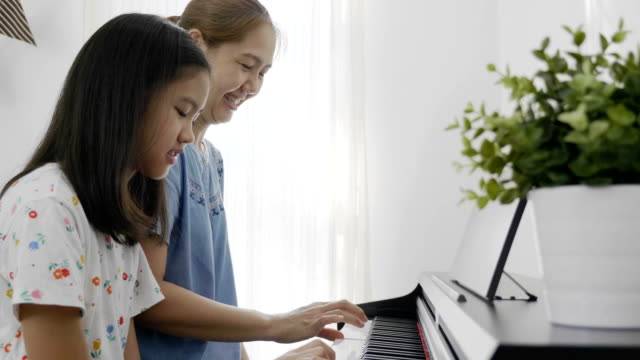 Slow motion of Asian girl playing piano with her mother, Zoom out video
