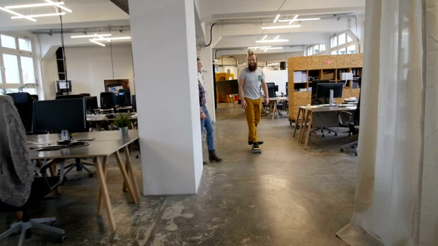 Slow motion of businesswoman looking at colleague skateboarding video