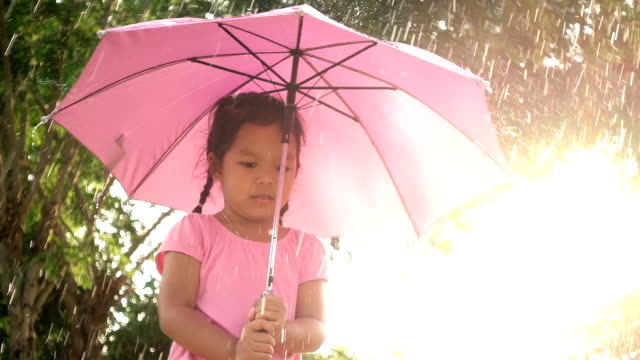 Slow motion of cute asian little girl holding umbrella and having fun to play with the rain and sunlight video
