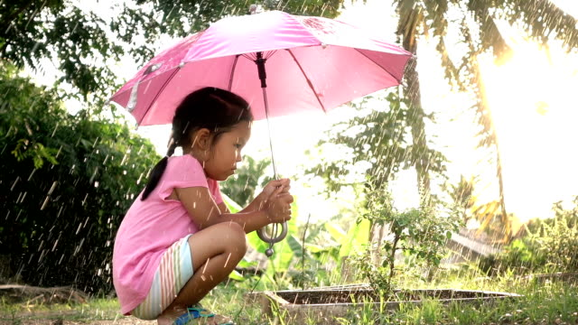 Slow motion of cute asian little girl sitting near the small tree and holding umbrella in the rainy day video