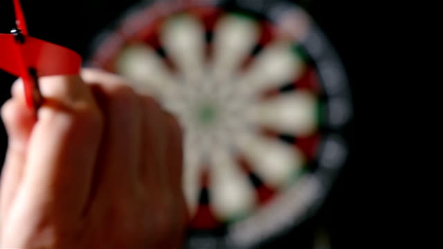 Slow motion of darts player throwing darts, defocused dart board on the background video