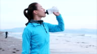 Slow motion of fit woman enjoying fresh air while drinking water on beach video