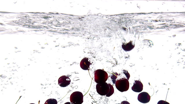 Slow motion of fresh cherry falling in water with splashes on white background video