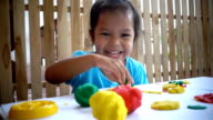 Slow motion of fun little girl with play dough modelling clay for kids video